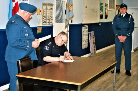 Dave Blancher signing his paperwork, making him an official CIC officer as Capt. Gerry Rempel and F.Sgt Anthony Ismay look on.  Photo credit: F.Sgt Corbin Johnson